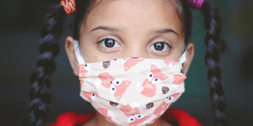 A small child with pigtails wearing a face mask with cartoon foxes on it.