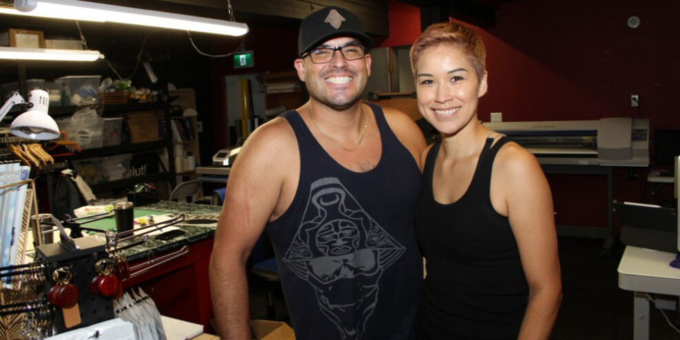Bill and Natasha Dennis with huge smiles in front of the equipment in their t-shirt printing shop.